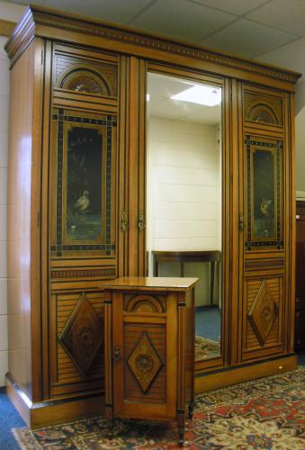Image of Lot  960  - A late Victorian Aesthetic movement walnut triple wardrobe with heron painted panels, together with a matching pot cupboard