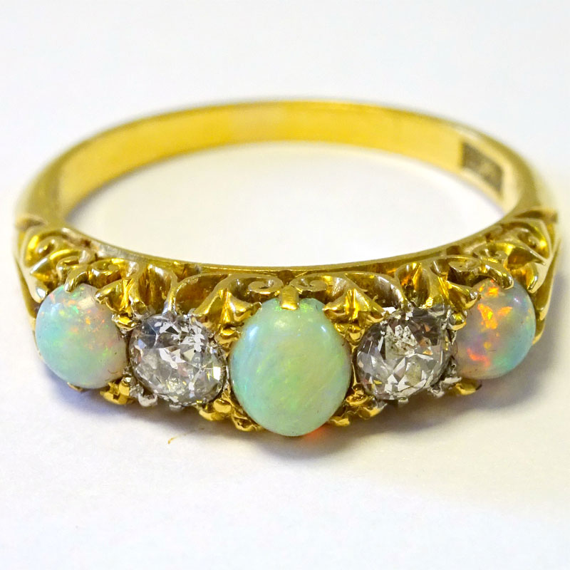 Image of Lot 141 - A five stone ring, yellow metal marked 18ct set with three cabochon cut opalescent stones and two old cut white stones
